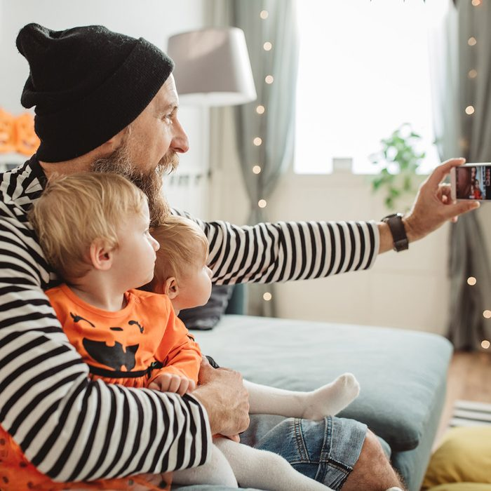 Cheerful Father With daughters celebrating Halloween At Home. They fooling around and wear costumes, father holding them on his knees and take selfie for social networks