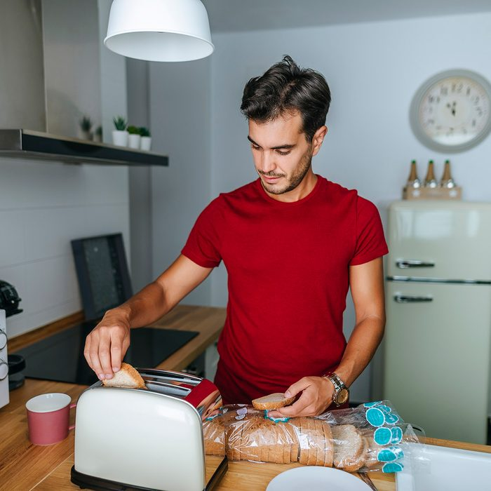 Man toasting bread with toaster in the kitchen
