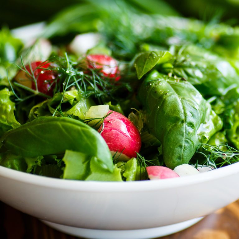 Spring salad from early vegetables, lettuce leaves, radishes and herbs in a white bowl crop