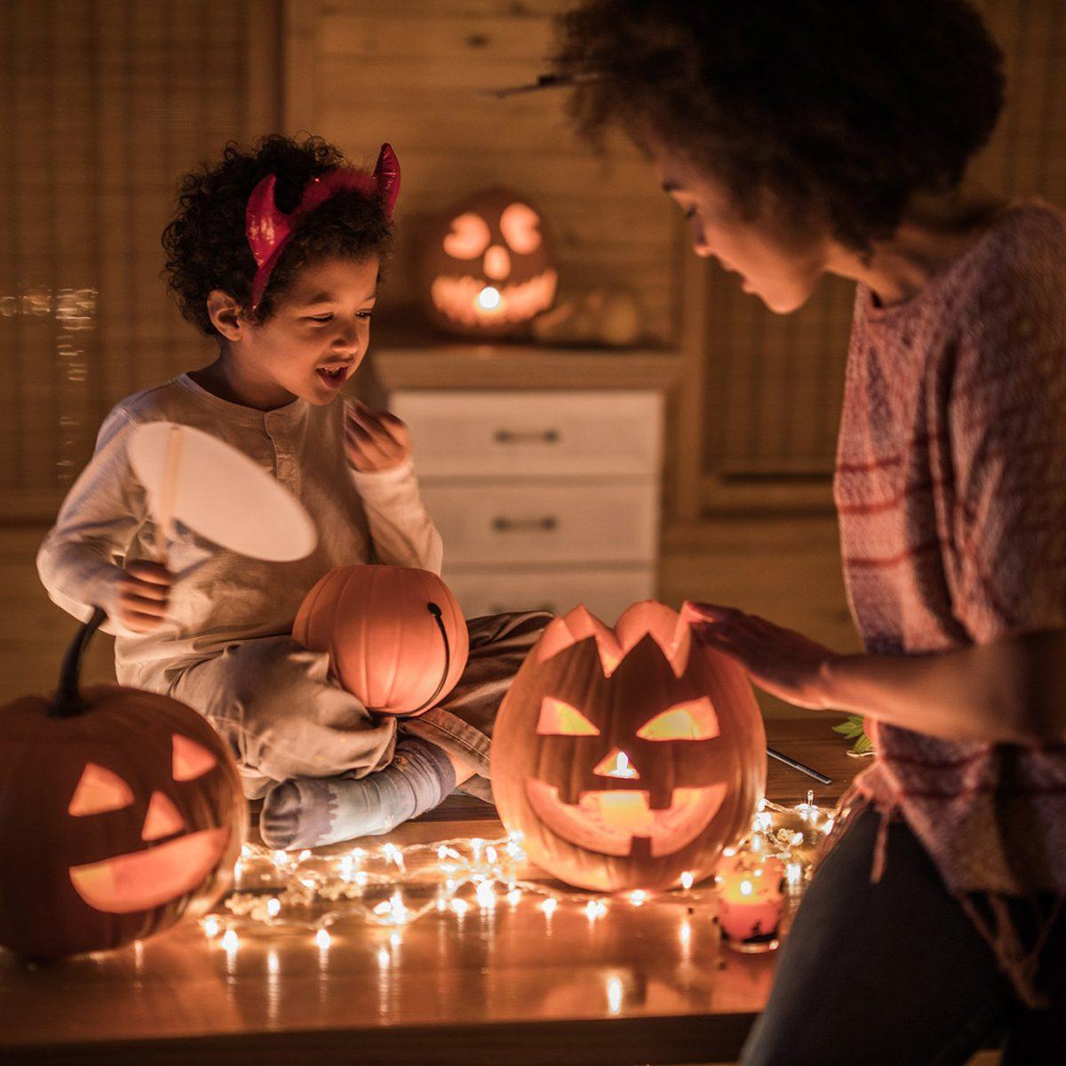 Mother and child lighting jack-o-lanterns