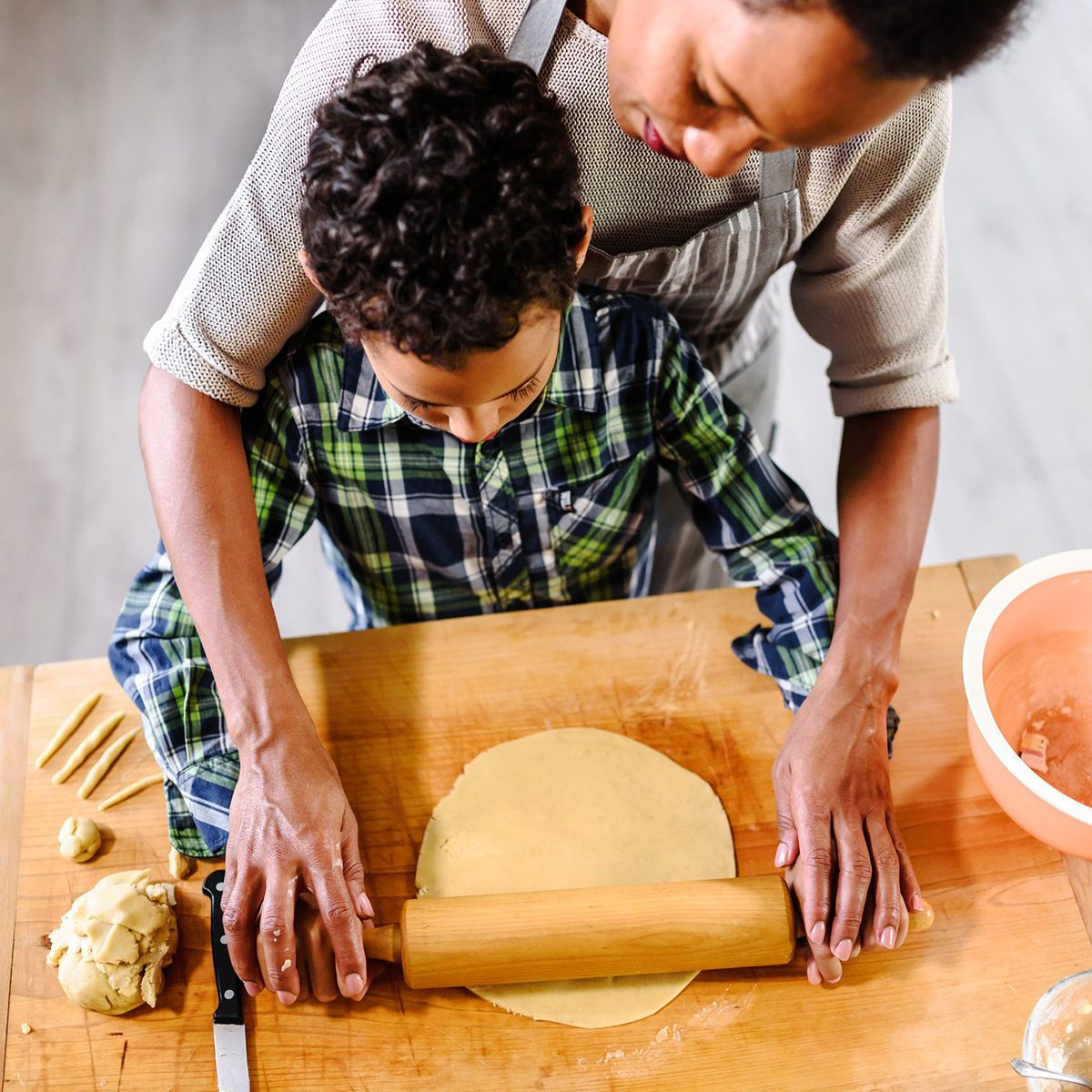 Mother and child rolling out dough together