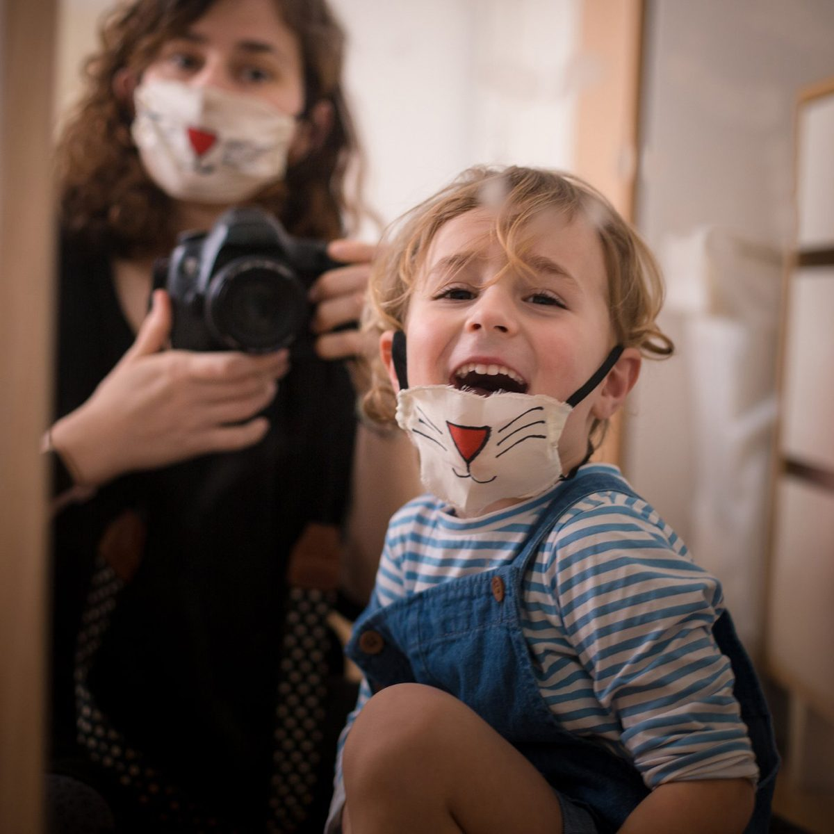 Mother and child wearing cat face masks