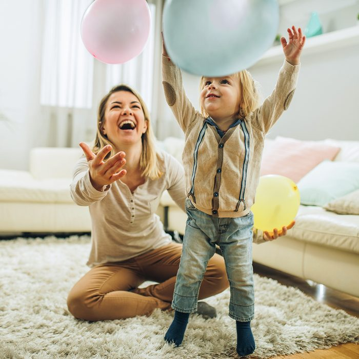 birthday party games for kids Happy mother and her small son playing with a balloons at home. Focus is on boy.