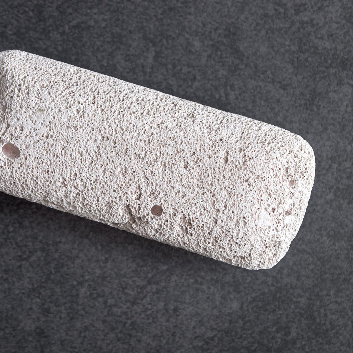 Raw pumice stone on table, light weight and with rough surface.