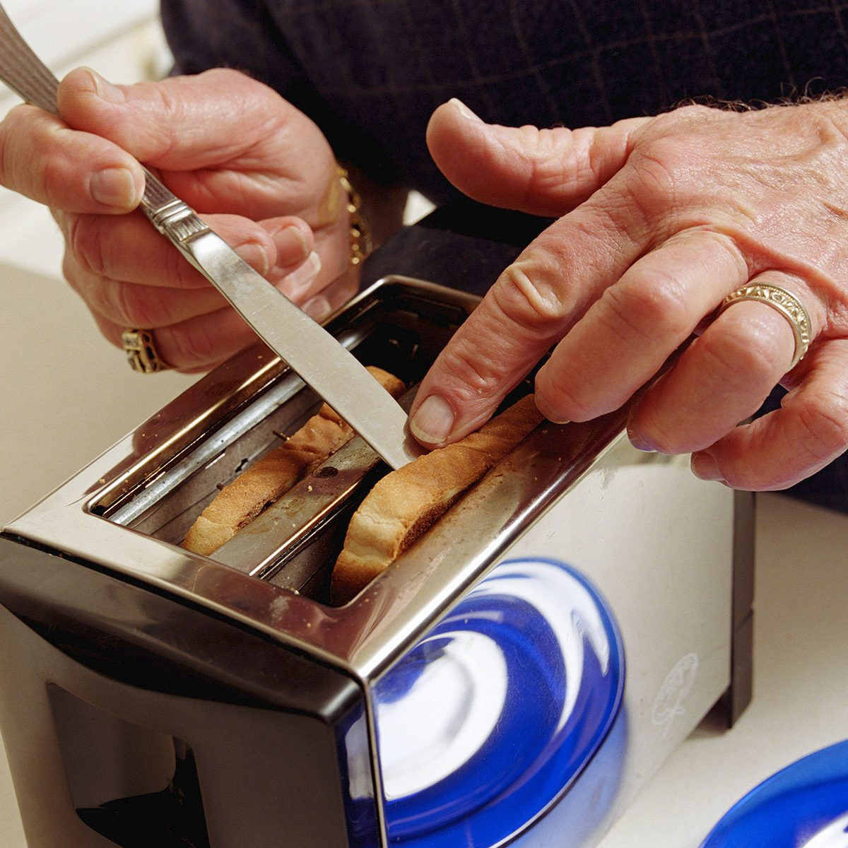 Senior man getting toast out of toaster with knife, close-up