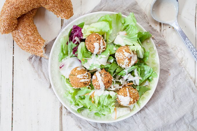 Kichererbsen-Falafel auf Salatbett mit Sesamring und Tahini-Sauce