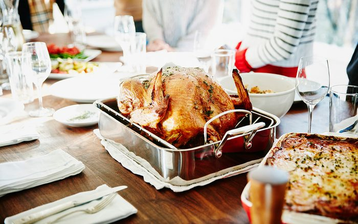 Turkey in roasting pan on table for holiday meal