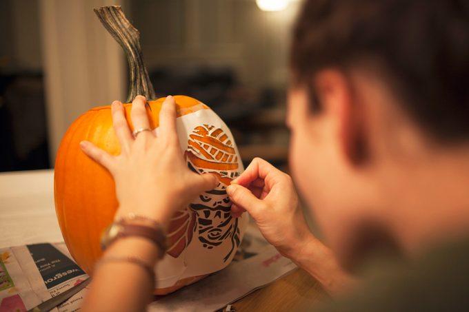 young woman stenciling a pumpkin
