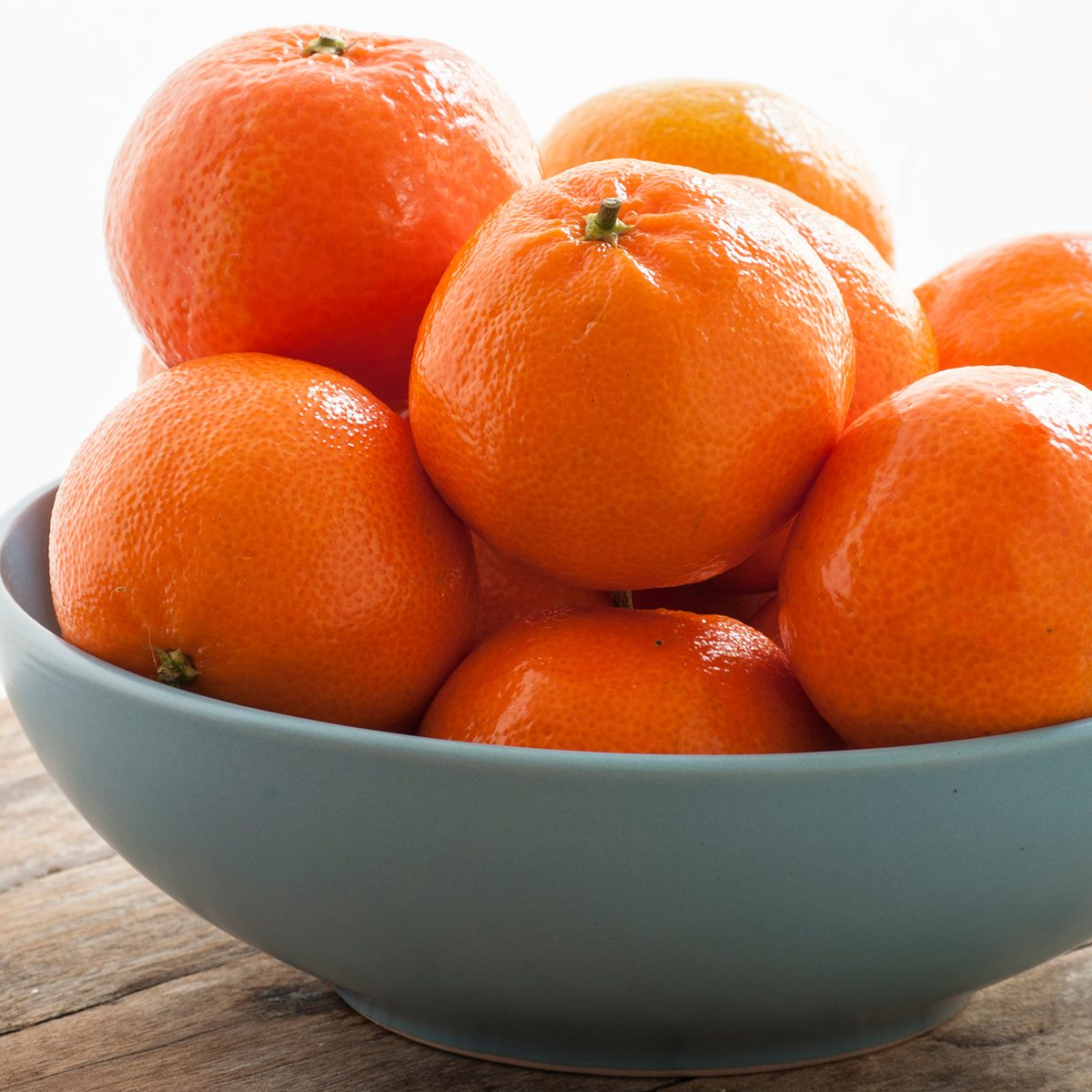 Close-Up Of Oranges In Bowl On Table Against White Background