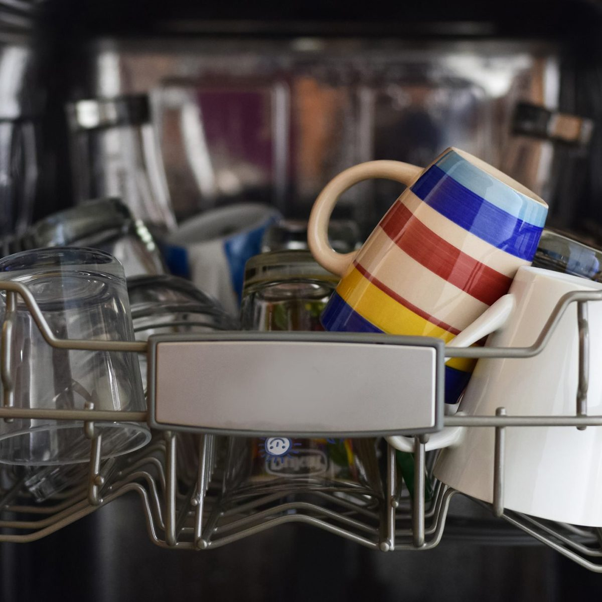 A close up of the top most rack of a dishwasher filled with glasses and cups