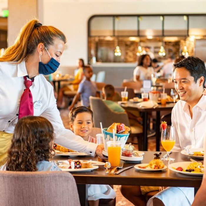LAKE BUENA VISTA, FL - JUNE 23: In this handout photo provided by Walt Disney World Resort, new measures are in place to promote health and well-being in table-service restaurants at Walt Disney World Resort on June 23, 2020 in Lake Buena Vista, Florida. Cast members wear appropriate face coverings at all times, while guests can only remove their face coverings while sitting at their table. Walt Disney World Resort will reopen on July 11, 2020. (Photo by Matt Stroshane/Walt Disney World Resort via Getty Images)