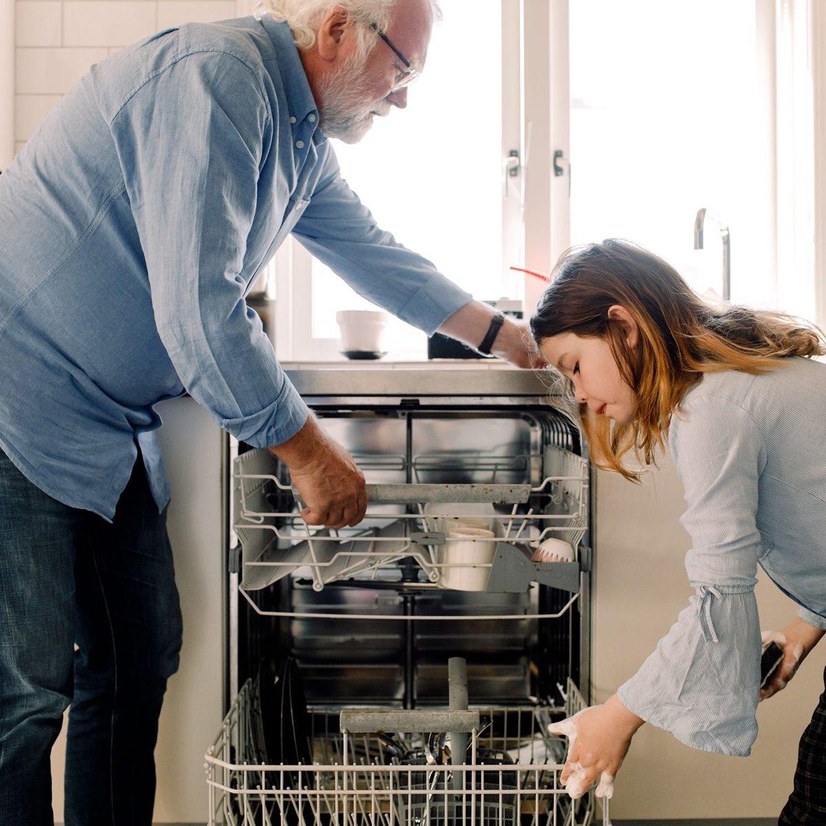 Grandpa and grandkid unloading dishwasher