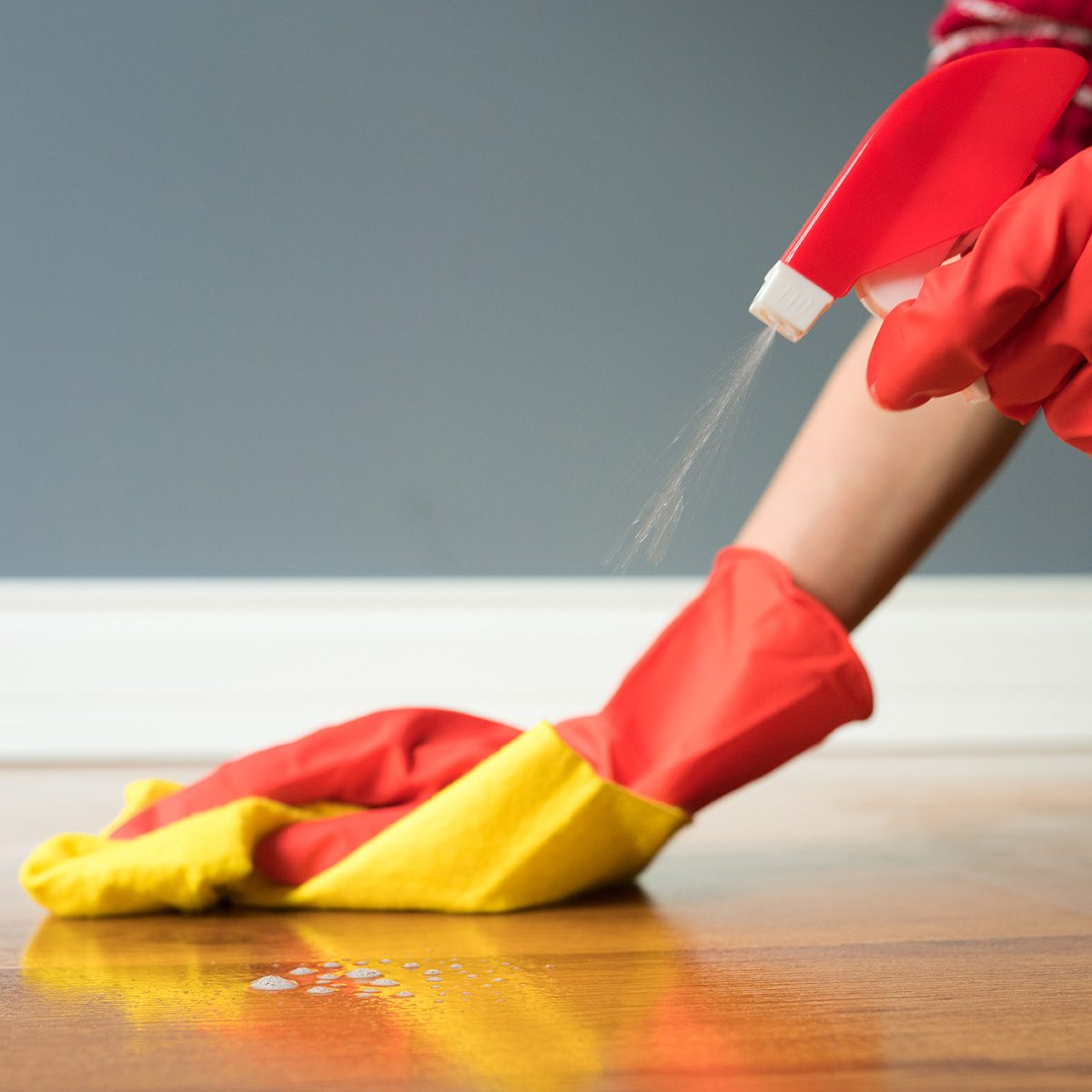 Cleaning parquet with yellow cloth