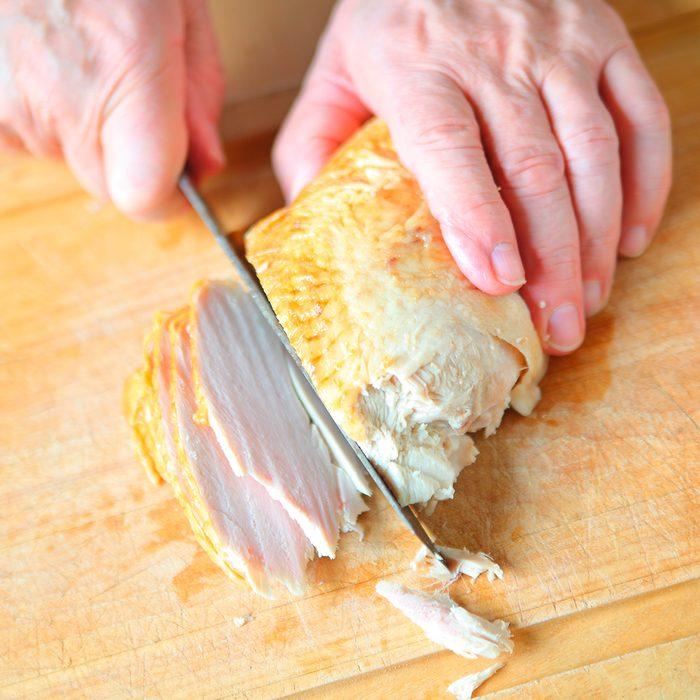 Man With Roast Turkey Breast On Cutting Board