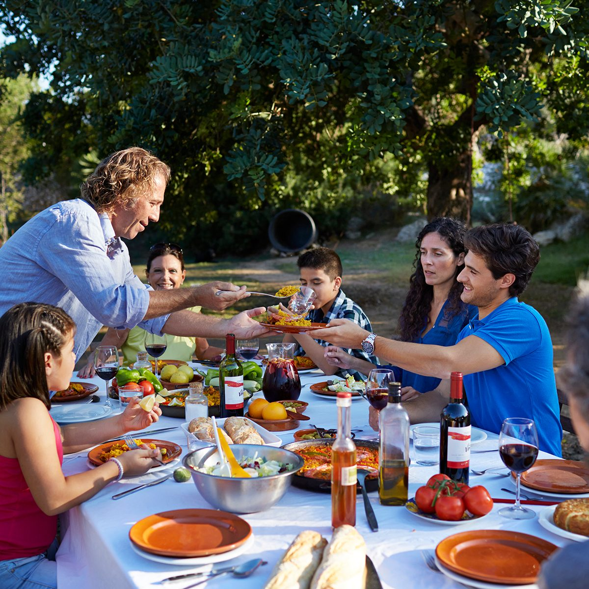 Multigenerational family together at dinner table at garden party in the sunset