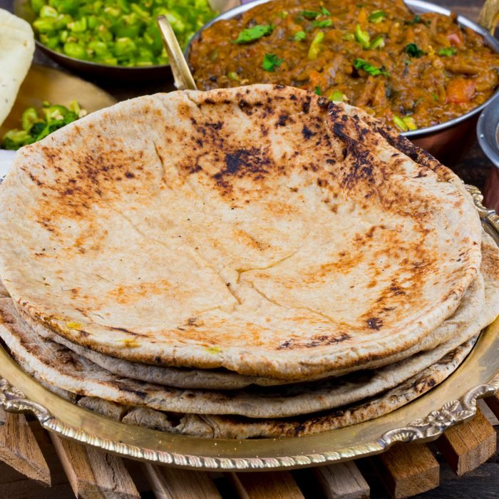 Indian Cuisine Chapati Also Called Roti, Flatbread, Chapathi or Chapatti Served With Sev Tamatar, Gatta Curry, Raita, Papad or Onion on Wooden Background
