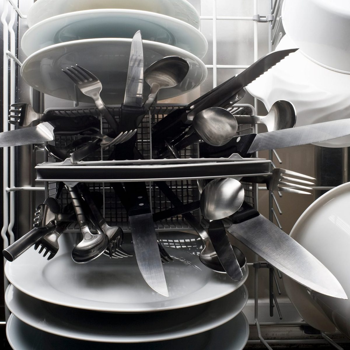 A dishwasher with knives sticking dangerously point side up