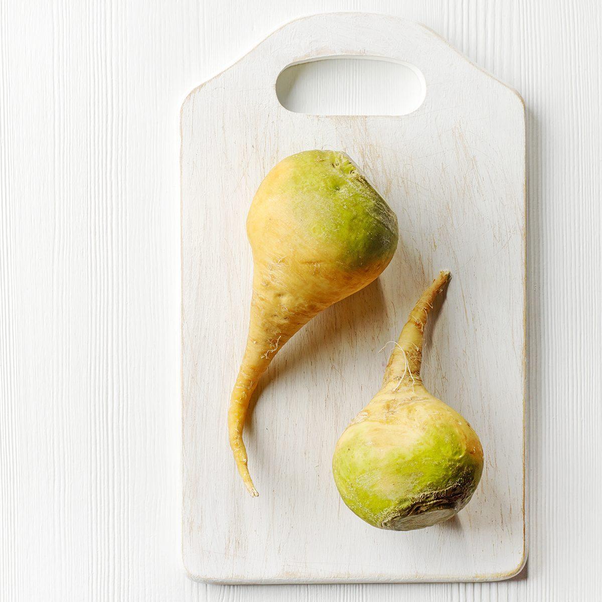 raw rutabaga on white cutting board