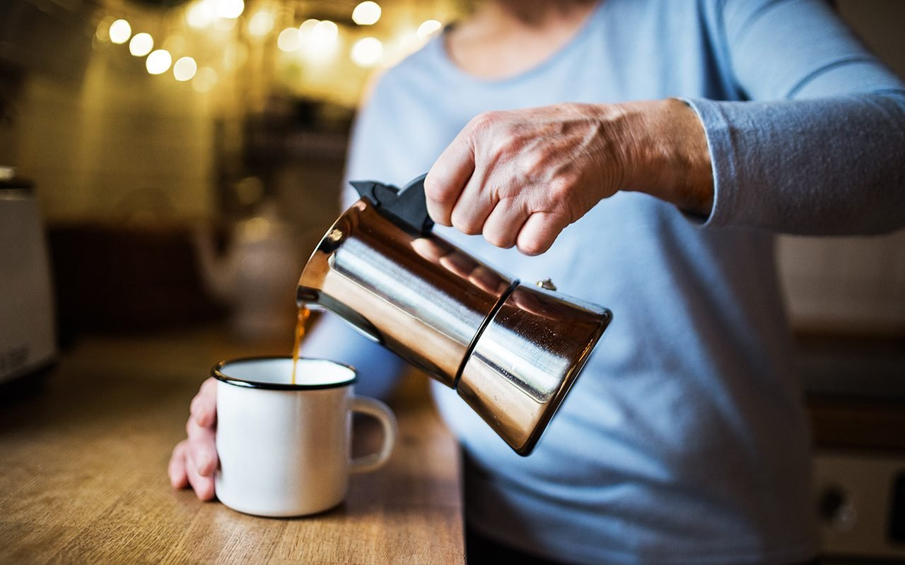 A close-up of an old lady pouring a cup of coffee into an enamel cup.