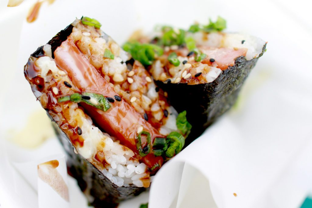 Spam musubi is a popular snack and lunch food in Hawaii composed of a slice of grilled Spam on top of a block of rice, wrapped together with nori dried seaweed in the tradition of Japanese omusubi.