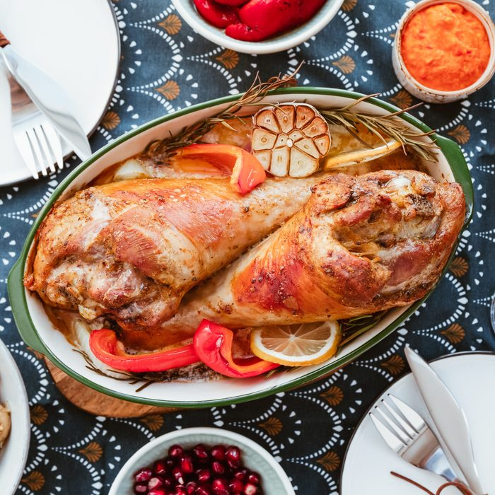 Festive dish for Thanksgiving, roasted turkey legs with vegetables on a table with snacks. Top view, flat lay.