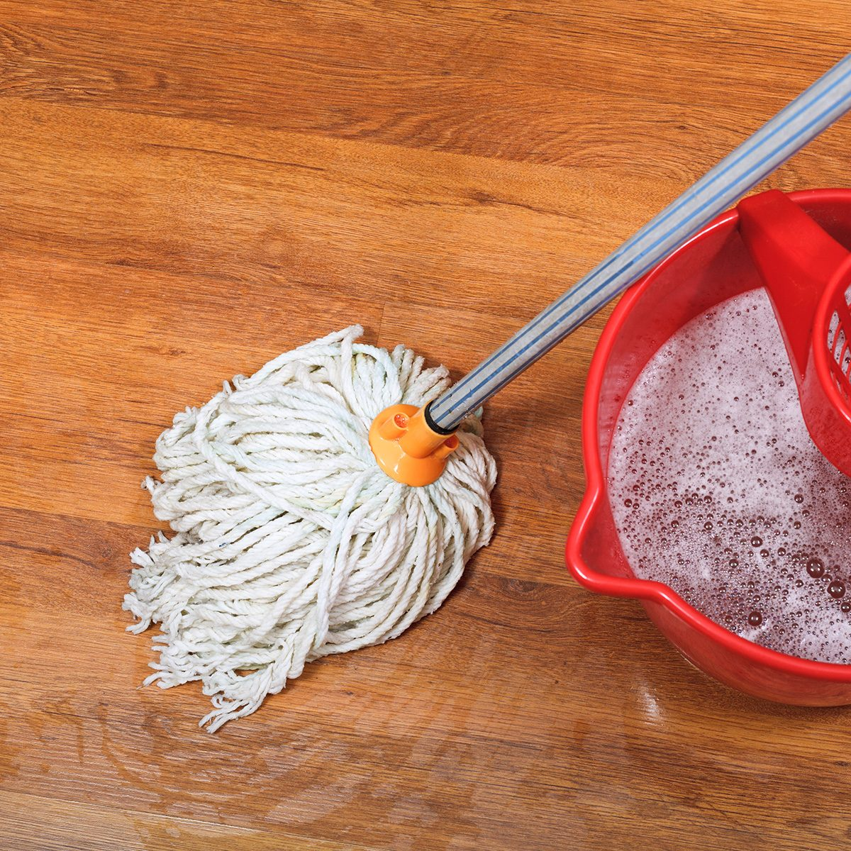 textile mop and red bucket on wooden wet floor