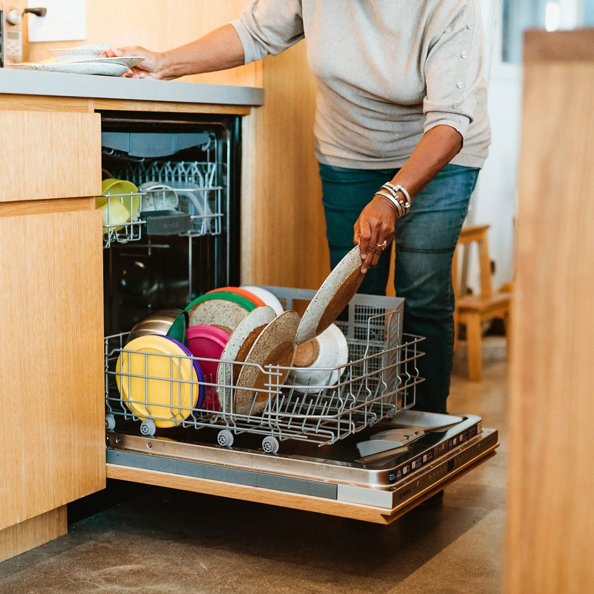 Low section of senior woman keeping plates in dishwasher. Retired female is doing routine chores in kitchen. She is in casuals at home.