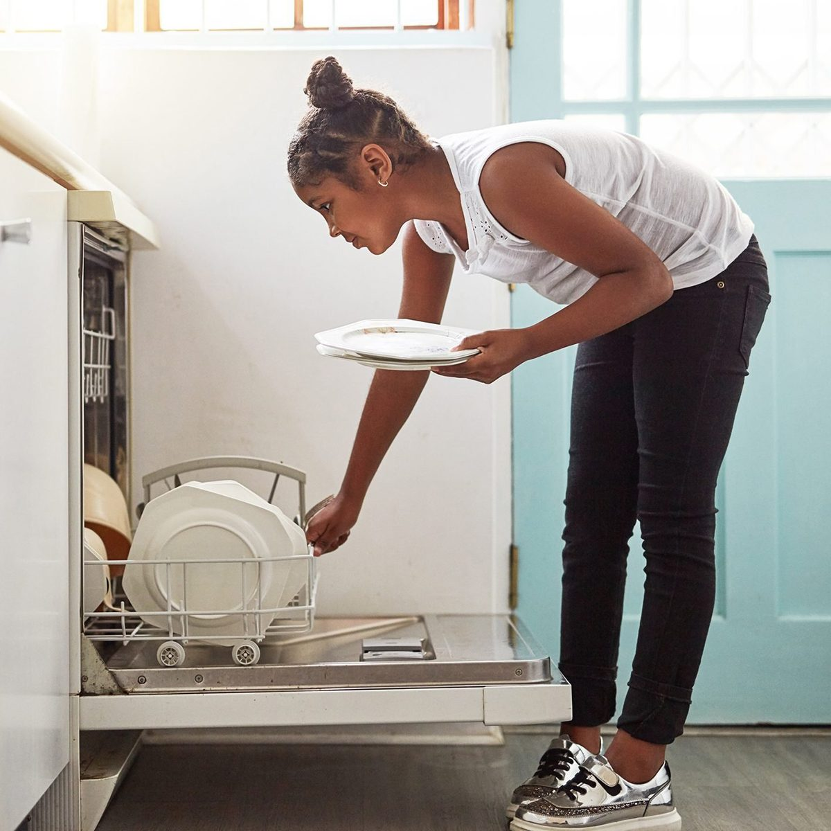 Shot of a young girl packing dishes in the dishwasher