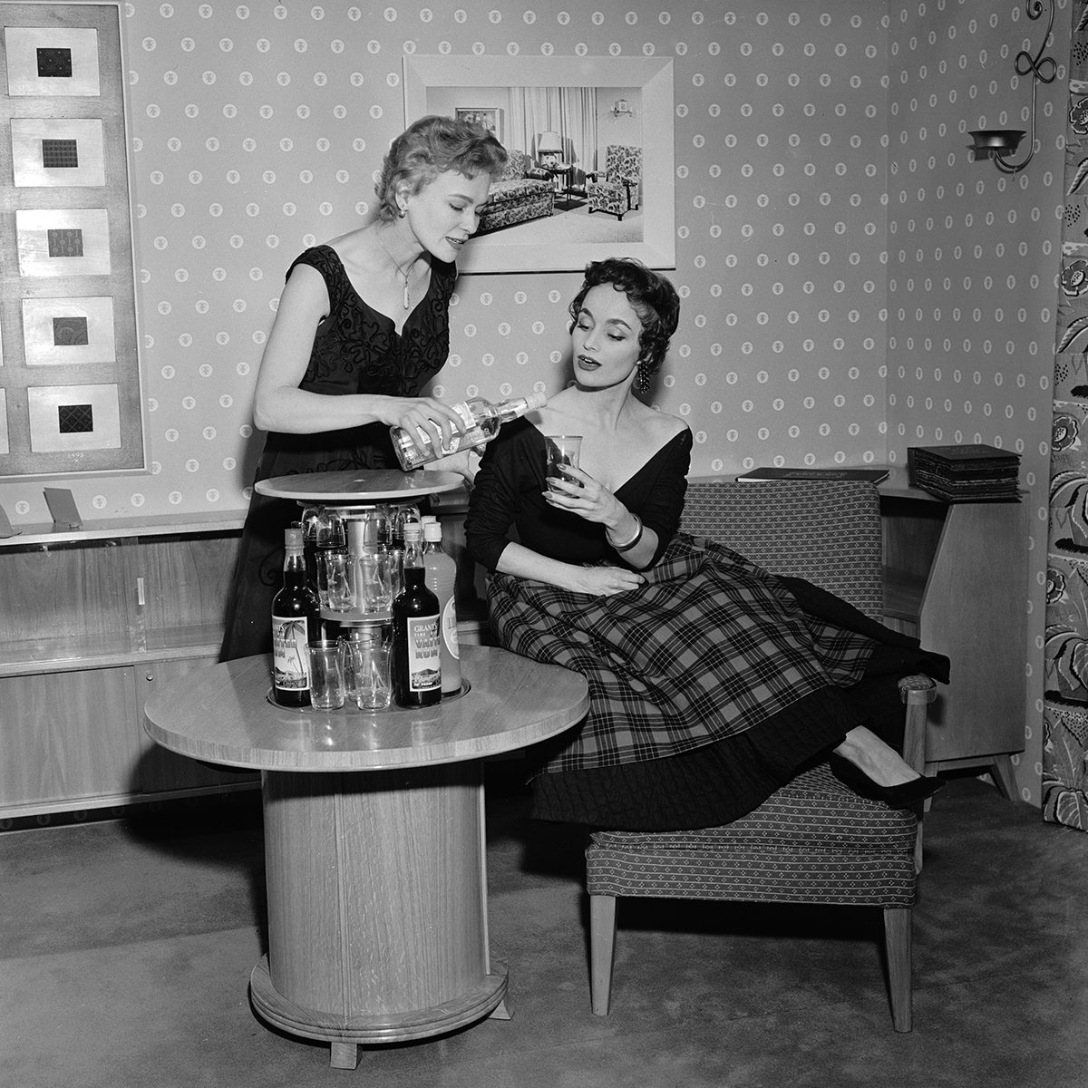 Models Jean Evans and Lynne Kennedy demostrating the push button cocktail cabinet at the British Furniture Exhibition at Earl's Court, London, 15th February 1954. The table has a concealed central section to store bottles and glasses which are revealed at the touch of a button. (Photo by Monty Fresco/Topical Press Agency/Getty Images)