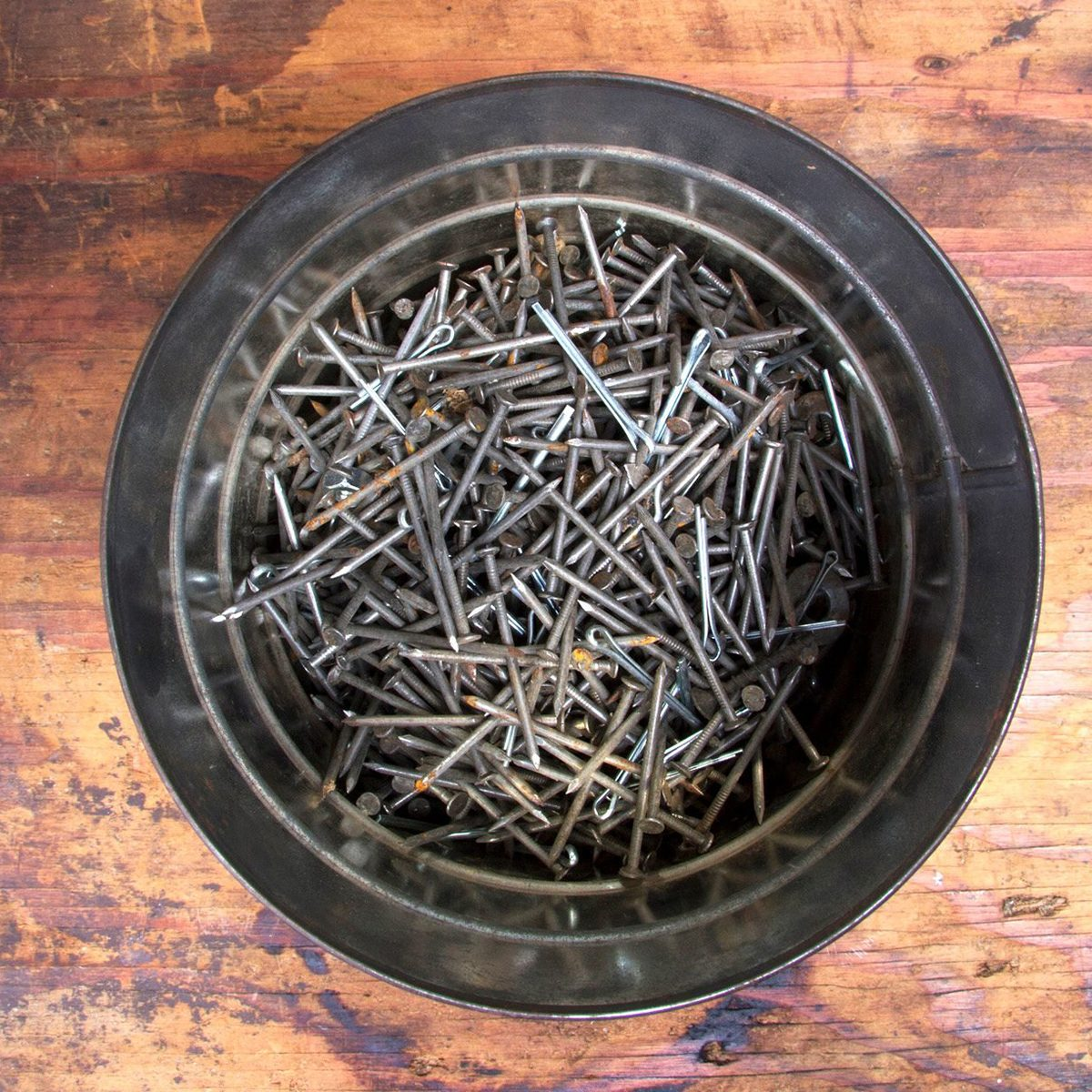 The garage staple of an old metal coffee can being used to hold assorted nails.