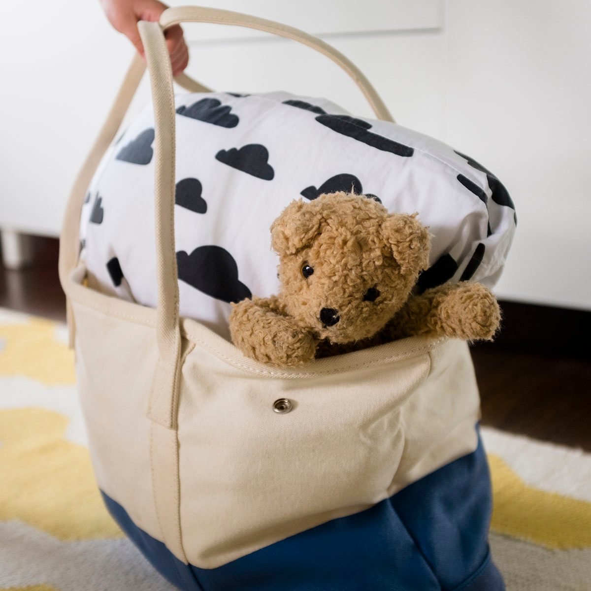 Girl's hand holding bag with blanket and teddy bear uses for reusable bags