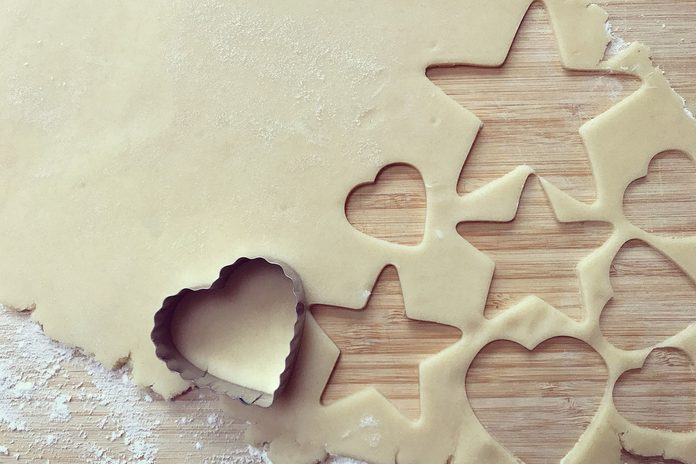 A cookie cutter on top of a piece of rolled-out cookie dough with lots of shapes cut out of it.