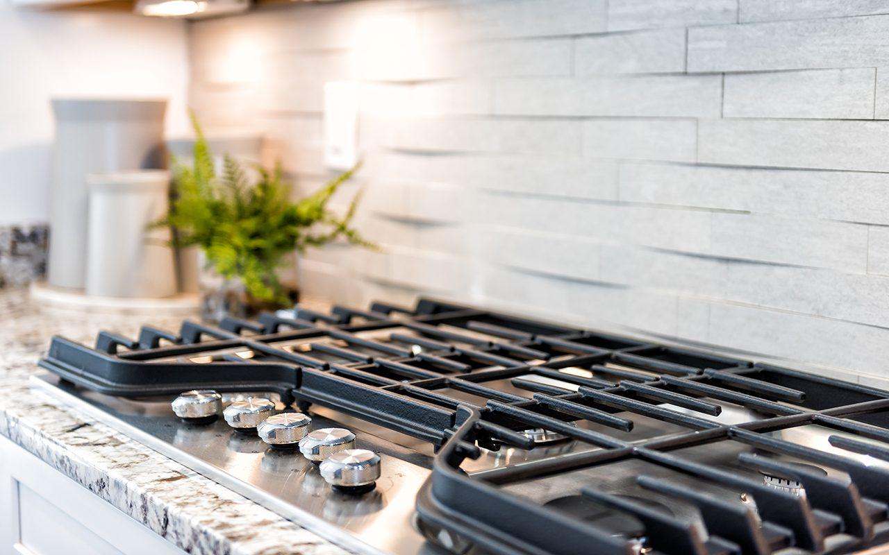 Macro closeup of modern luxury gas stove top with tiled backsplash