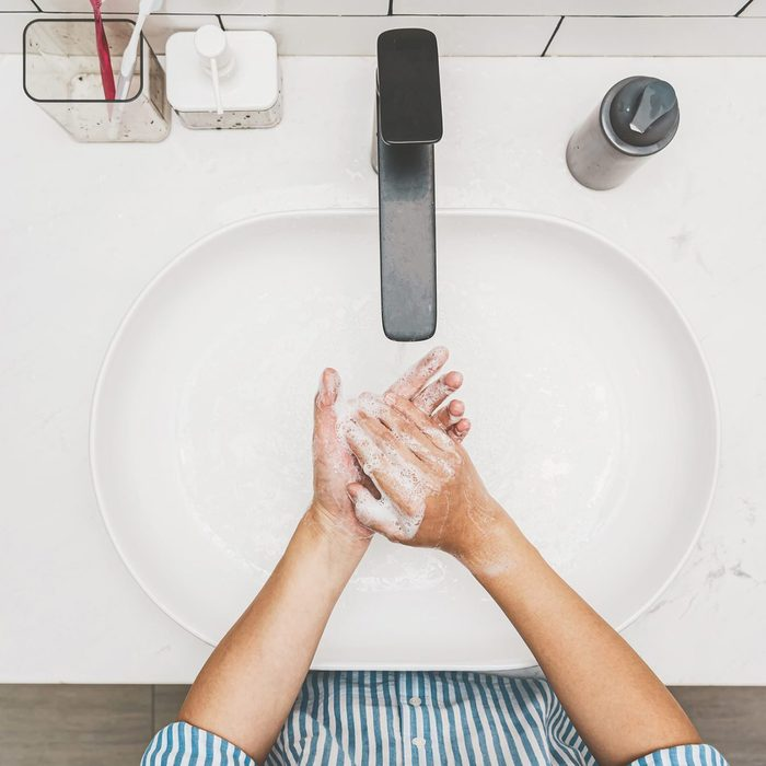 Health care of Covid-19 pandemic concept, Top view Asian hand washing with faucet water in Bathroom at home
