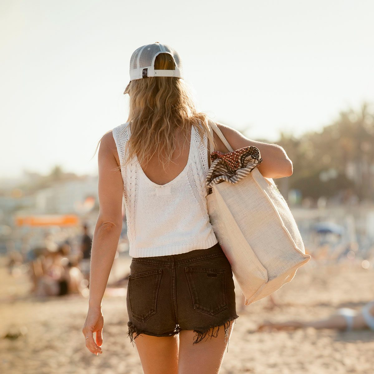 Woman walking along beach, rear view, Sitges, Catalonia, Spain uses for reusable bags
