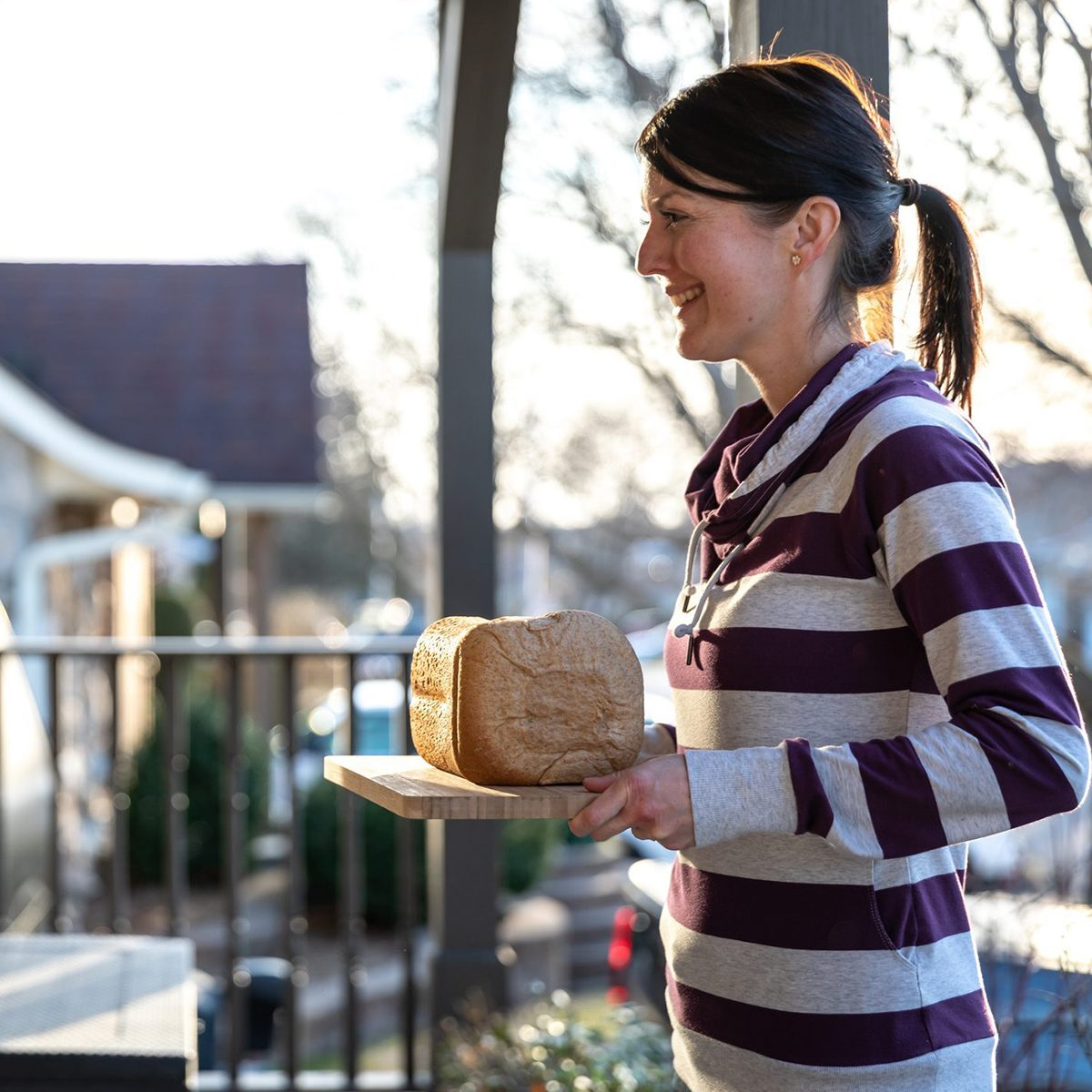 Young woman bringing homemade bread to neighbor's door at sunset during COVID-19 Crisis.