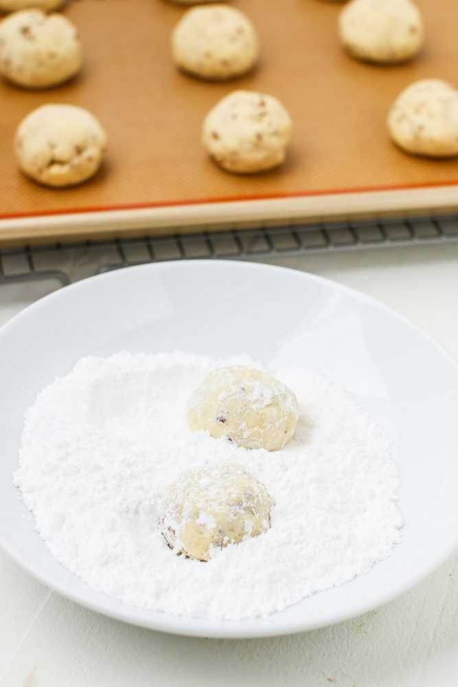 Rolling Cookies in Powdered Sugar - how to make snowball cookies from scratch