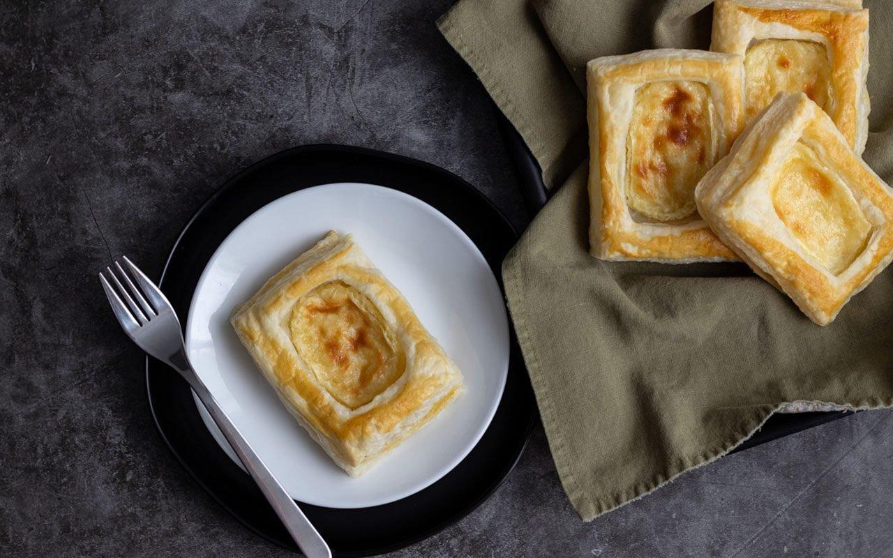 Danish on a plate next to tray of more Danish. starbucks cheese danish copycat