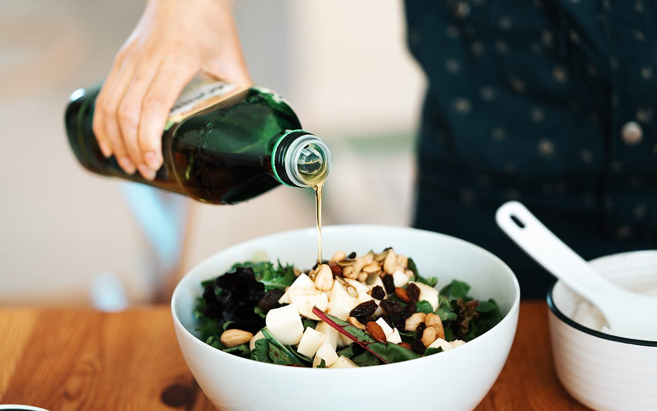 how to store olive oil Close-up view of a bowl of fresh green salad with mozzarella, mixed nuts and dry fruits. A woman's hand was pouring olive oil into the salad.