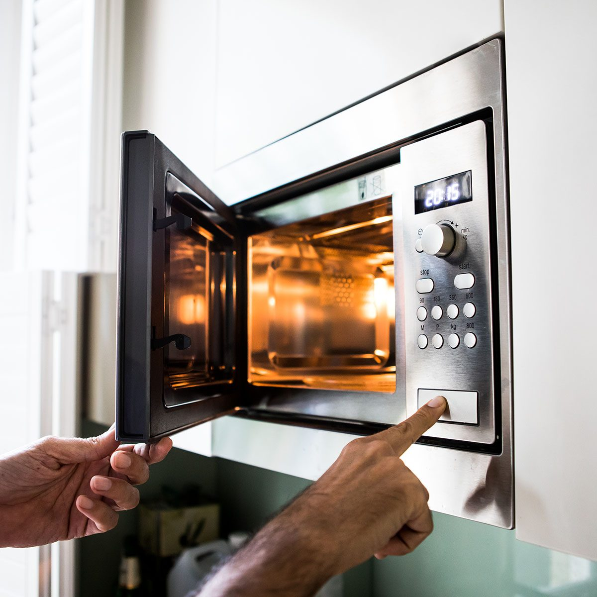A man using a microwave oven. His finger on the opening button.