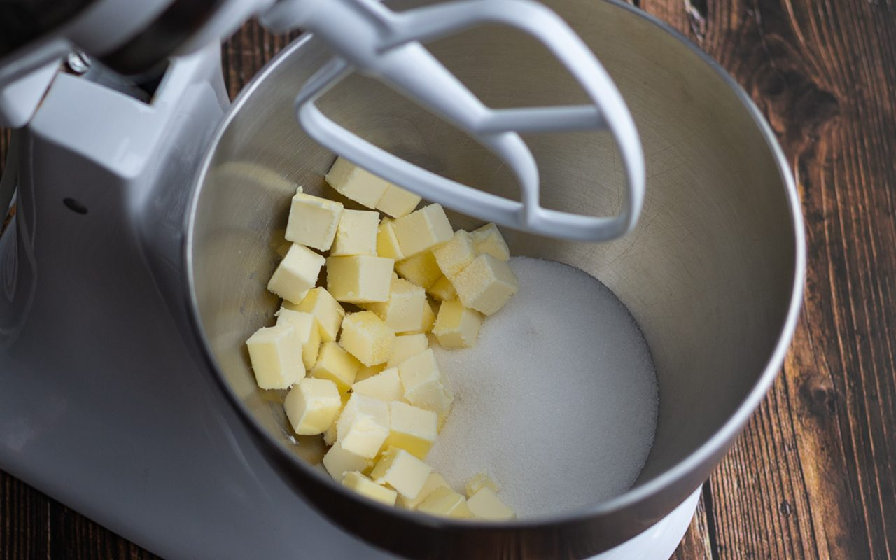 how to cream butter and sugar Stand mixer bowl with sugar and cubes of butter.