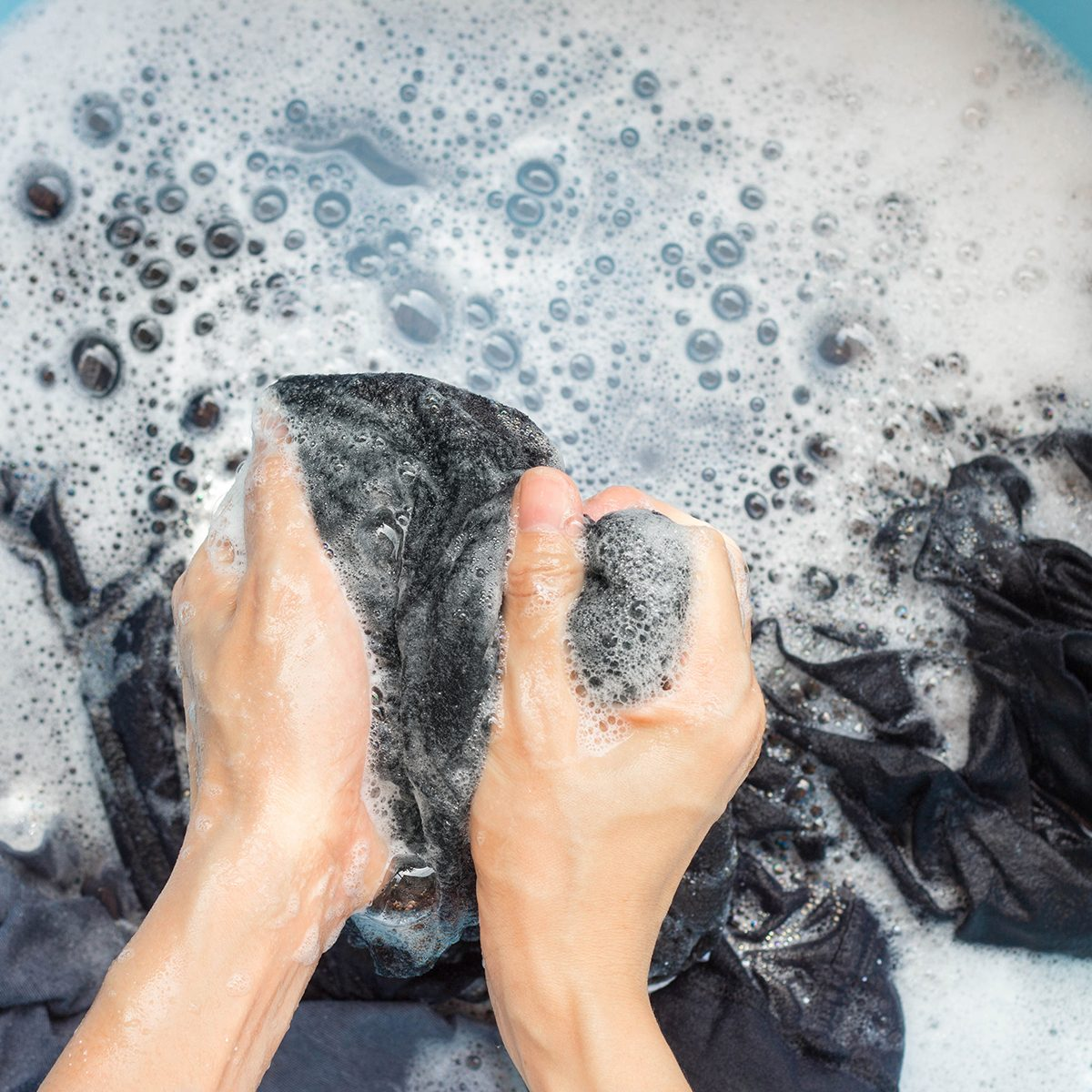 Cropped Hands Of Person Washing Laundry In Bucket