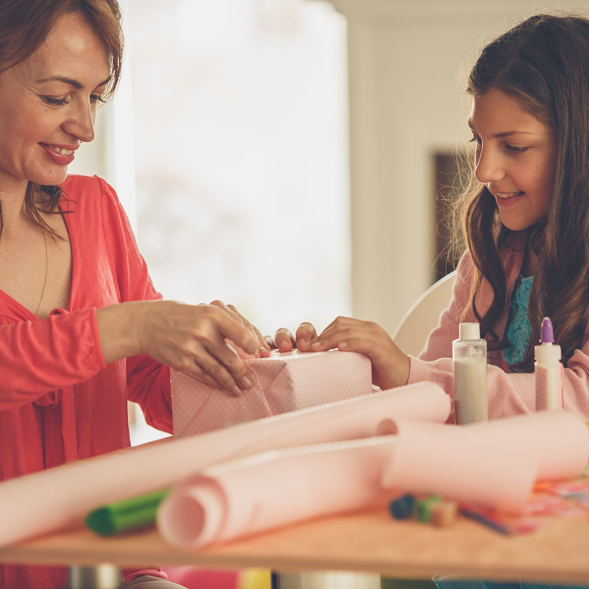 Happy Mother And Daughter Wrapping A Present Together