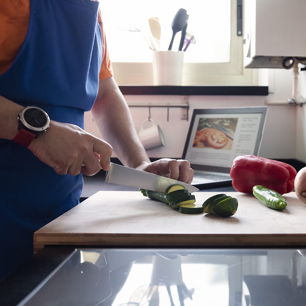 Man Cutting Vegetables In The Kitchen At Home