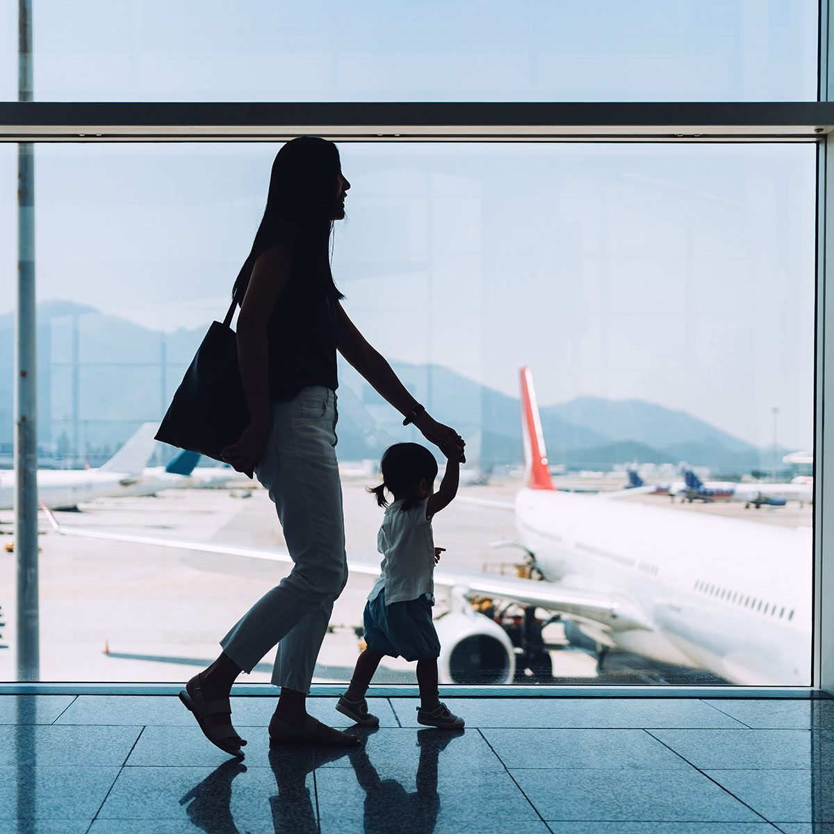 Silhouette of joyful young Asian mother holding hands of cute little daughter looking at airplane through window at the airport while waiting for departure uses for reusable bags