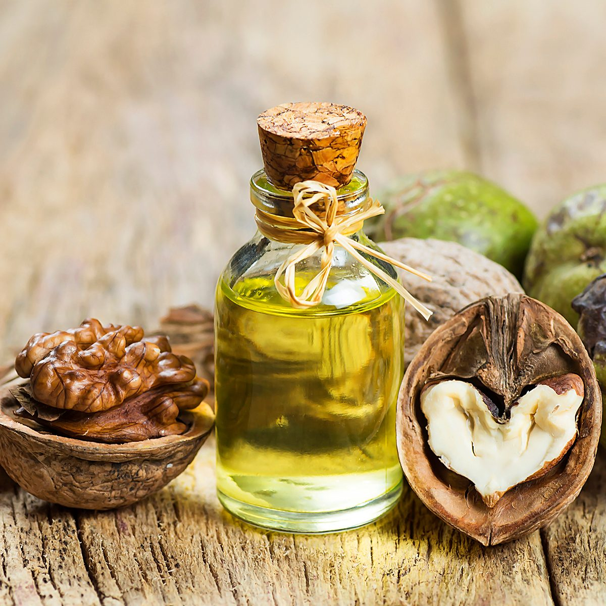 healthy oils Walnut oil in glass of bottle, whole big peeled walnut kernel with thin shell on wooden background. healthy food for brain. Fresh walnuts background nut concept