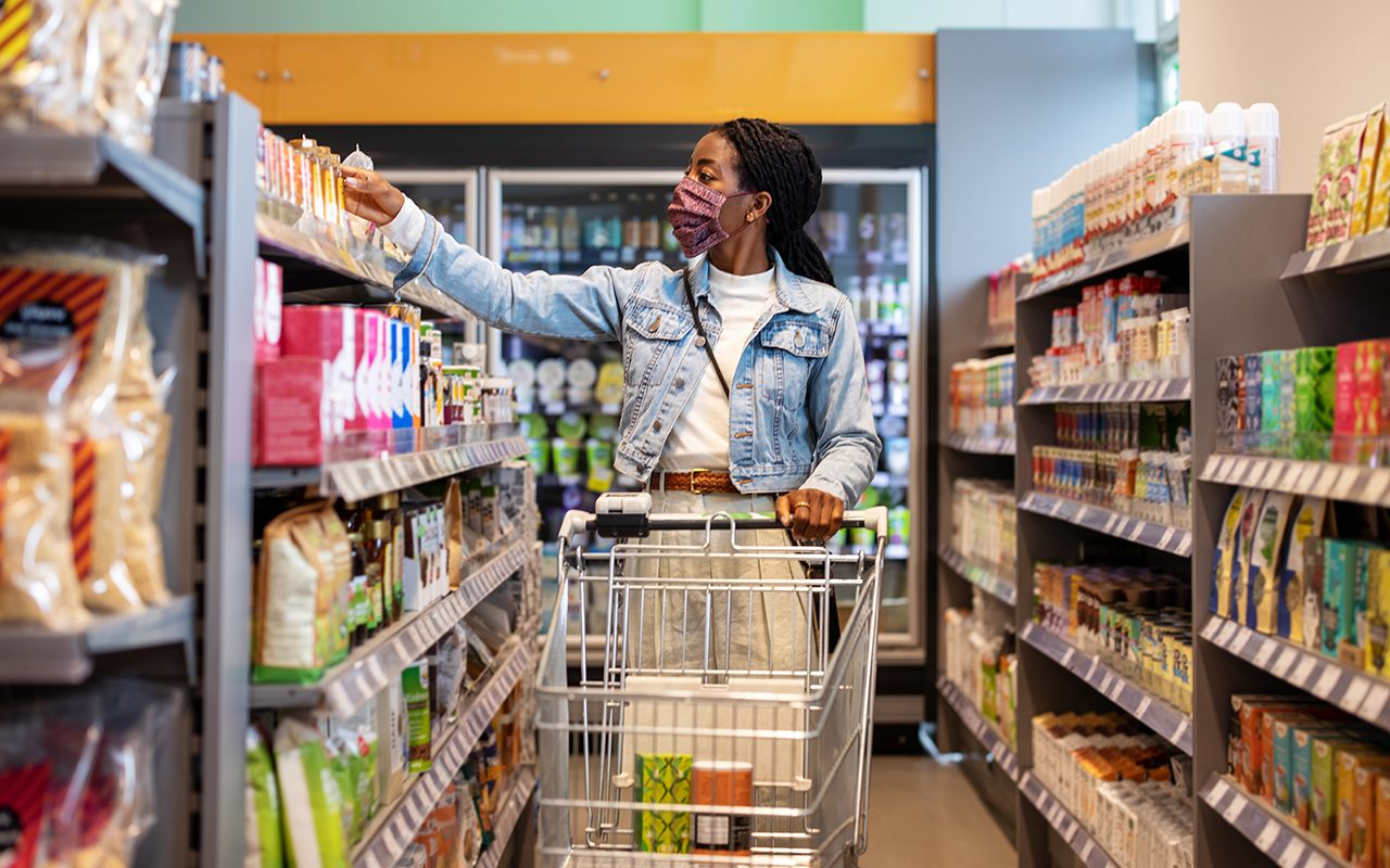 Female customer with a face mask buying groceries at a supermarket. Woman choosing a product from the rack in local grocery store.