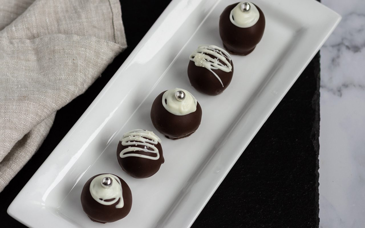 Chocolate coated truffles on a long white plate. How To Make Chocolate Truffles.toh.nancy Mock 6