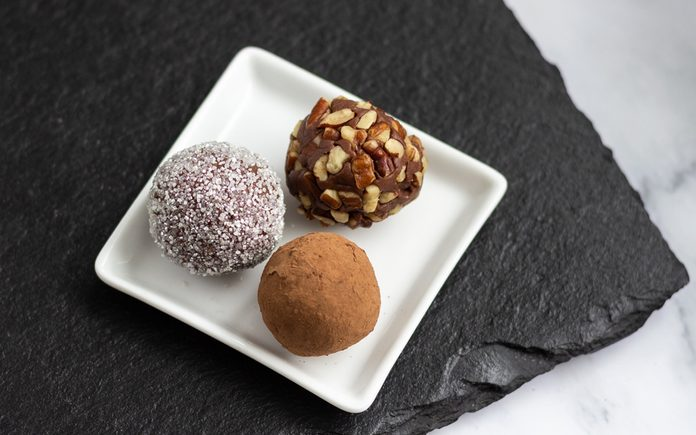 Three chocolate truffles on a white plate. How To Make Chocolate Truffles.toh.nancy Mock 7