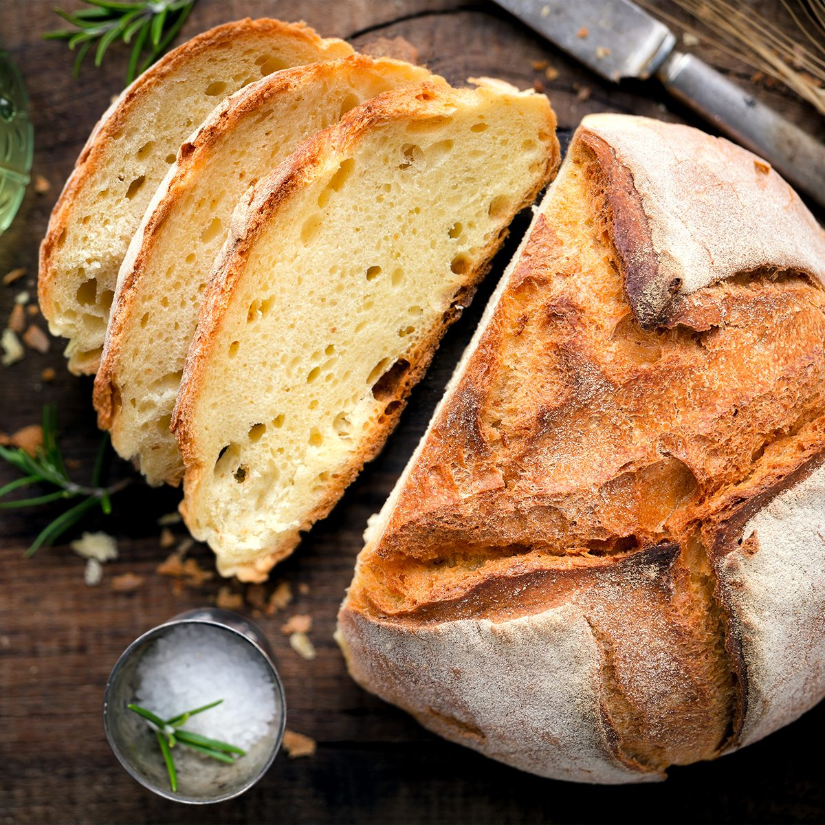 Rustic loaf of homemade bread served with olive oil, rosemary and salt on dark wooden table. Overhead view